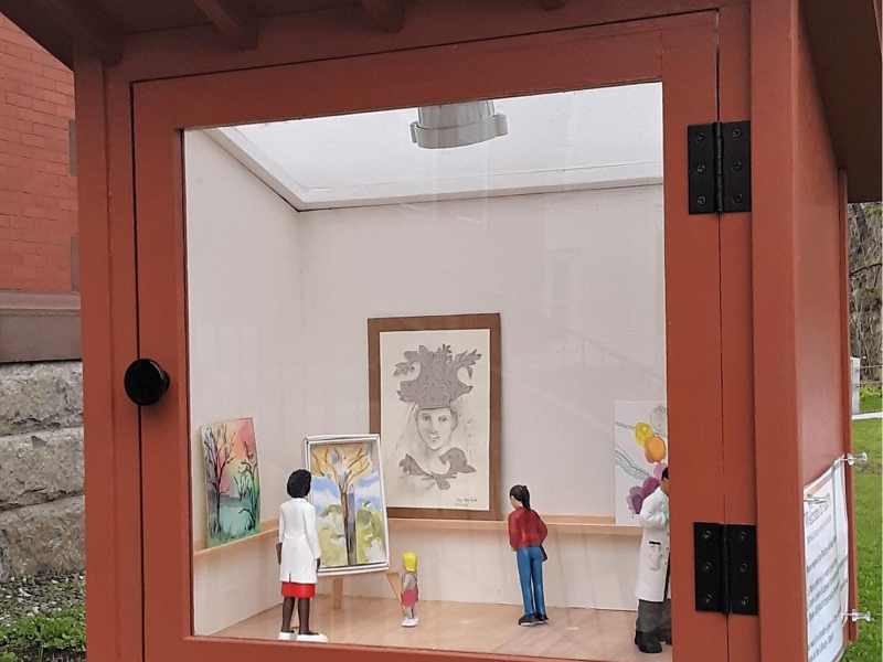 Tiny red building with glass door. Through the door there is a tiny art gallery complete with miniat